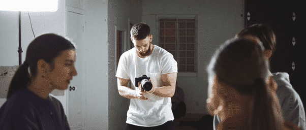 man in white t shirt pointing a camera at actors